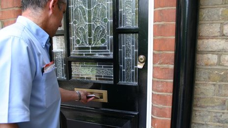 Postie delivering letter through letterbox