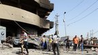 Residents assess the damage caused by a bomb attack in central Baghdad