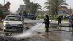 A firefighter cleans the cite of a bomb attack in the Shia southern city of Hilla