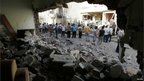 Residents look at the damage caused to a building in a bomb blast in Kirkuk