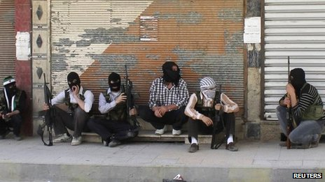 Free Syrian Army members, with covered faces and holding weapons, sit by the side of a street in Qaboun district, Damascus June 11, 2012.
