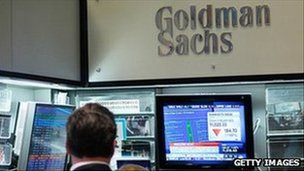 Goldman Sachs logo above trading screens