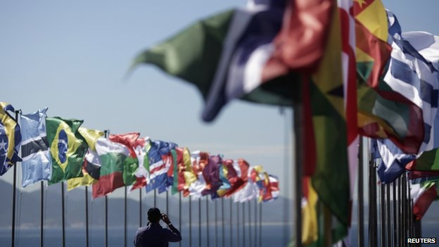 A man takes picture of national flags fluttering at the Copacabana Fort