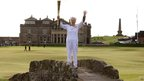 Louise Martin holds the Olympic Flame on the Swilken Bridge on the 18th hole on the Old Course at St Andrews