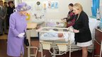 Queen Elizabeth II meets newborn babies as she visits a new maternity ward at the Lister Hospital