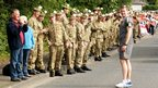 Members of the second battalion of the Royal Highland Fusiliers wait for the torch relay to pass through Milton Bridge, 14 June 2012