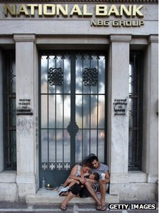 A family beg on the street in front of the offices of National Bank on June 14, 2012 in Athens, Greece.