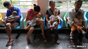 People holding babies who drank tainted milk powders queue to receive examination in a Hospital in Wuhan, China, 17 Sept 2008