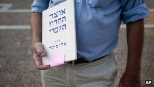Israeli author Eli Tziper holds his book The Treasure of the Hebrew Rhyme