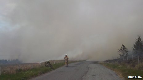 Firefighter amid smoke from heath fire