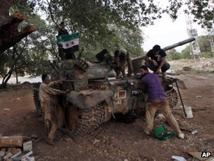 Members of the rebel Free Syrian Army carry out work on a captured tank in Idlib province (13 June 2012)