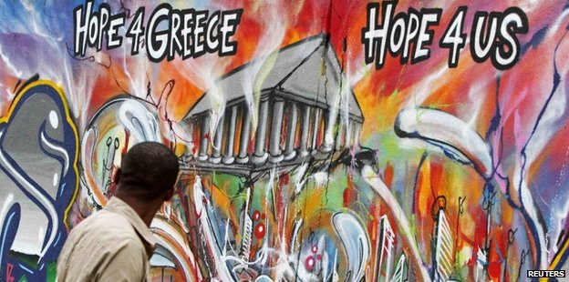 Man walking past Athens graffiti