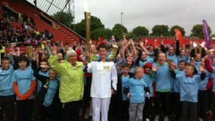 Torchbearer holding flame aloft in stadium