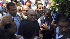 Former prime minister and current presidential candidate Ahmed Shafik (C) leaves a polling station after casting his vote in Cairo
