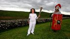 Charlotte Proud carries the flame along Hadrian's Wall at Housesteads Roman Fort in Northumberland, 16 June 2012