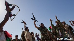 Libyan rebel soldiers from Bengazi celebrate as they arrive on an ex-Libyan Army frigate on August 30, 2011 in Tripoli, Libya