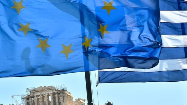 EU and Greek flags float in front of the Acropolis in central Athens
