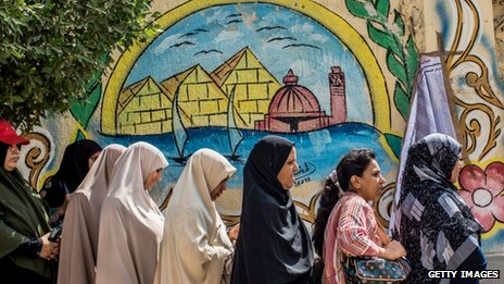 Egyptian women line-up to cast their vote, as a list with the names of local residents registered to vote, hangs on the wall at a polling station on June 16, 2012 in Giza, Egypt