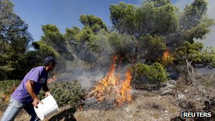 A resident tries to extinguish a forest fire at Palaia Fokea coastal village a few miles south of Athens