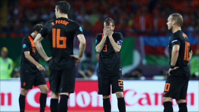 Holland's players are dejected after conceding a second goal