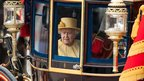 The Queen riding in a vintage carriage