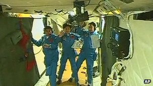 The three Chinese astronauts waving to cameras from Tiangong 1 space lab
