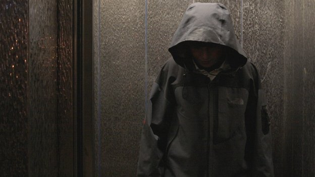 A teenage boy wearing a hooded jacket.