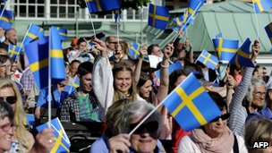 People wave the Swedish flag