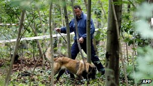 French policeman carries out investigations at the Bois de Vincennes in Paris on 18 June, 2012 after a second headless human torso was discovered in the woods.