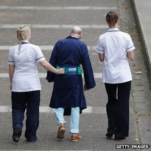Two NHS staff walk with an elderly patient