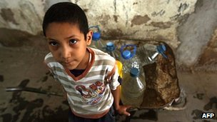 Yemeni boy waits for his turn to fill water bottles