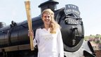 Kelly Williams posing with her torch in front of the steam locomotive The Green Knight