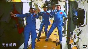 Chinese astronauts wave to camera on board of the Tiangong-1 space lab, 18 June 2012