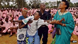An unknown woman survivor of the 1994 Rwandan genocide is taken away by family members and by a policeman in Butare's stadium 29 September 2002, where more than 2,000 prisoners suspected of taking part in the genocide were made to face the victims of the massacre
