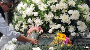 A tourist leaves flowers on Pablo Escobar's grave in Medellin - file photo