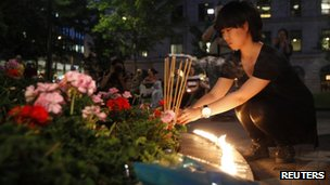 A woman burns incense as part of a candlelight vigil for Jun Lin in Montreal on 14 June 2012
