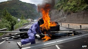 A masked miner climbs over a barricade which includes a burning tyre