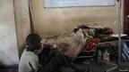A boy sits with a sick relative at a hospital in Juba, South Sudan