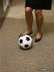 Woman dribbling football in office corridor