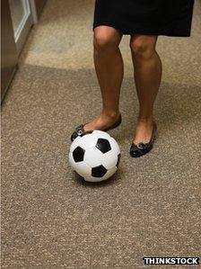 Woman dribbling football in office corridor