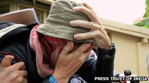 Pascal Mazurier with face covered and hat on when arrested