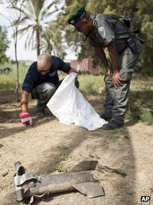 Israeli border police officer and police engineer examine the remains of a rocket fired by militants from Gaza (20 June 2012)
