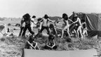 20 June 1978: Rock fans dancing in a ring on the top of a knoll with Stonehenge in the distance, at a music festival.