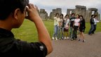 Tourists pose for a photograph in front of Stonehenge in August, 2002.