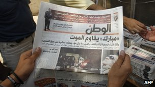An Egyptian reads a newspaper with front page news about the health of ousted president Hosni Mubarak
