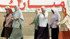 """Egyptian women pass a huge banner that reads: """"Mubarak: Stability, Development and Prosperity"""" on their way to a polling station on 26 September 1999 in Cairo"""