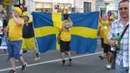 Swedish fans hold flag in fan zone