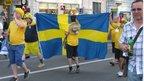 Swedish fans hold flag in fan zone