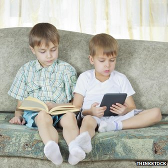 Two boys, one reading a book, one an e-reader