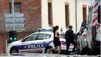 Two people run between police cars outside the CIC bank in Toulouse